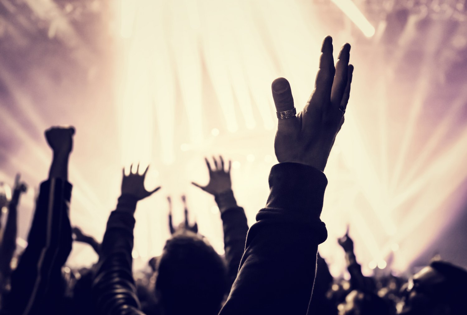 Grunge style photo of silhouette of people hands raised up on musical concert, enjoying music, dance